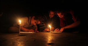 Palestinian children study on candles light during a power cut in Deir al-Balah